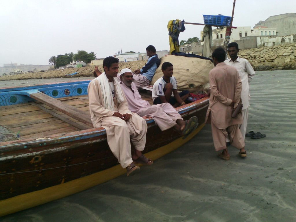 Fisherman stand next to their vessel in Gwadar